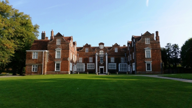 Christchurch Mansion, red brick building with white pillars and expansive lawn at front