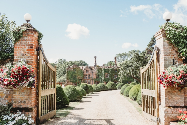 Seckford Hall Hotel & Spa, gates at start of gravel drive with hedgerows leading to red brick ivy clad house