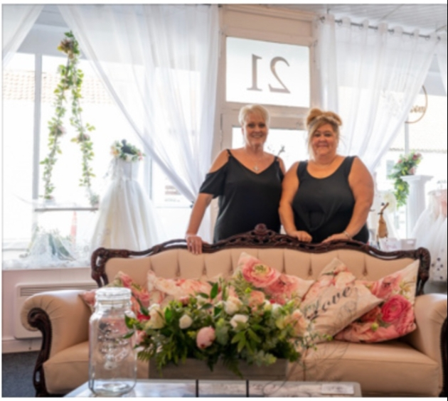 Owners standing behind sofa in shop