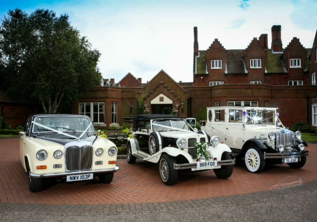 row of three vintage wedding cars outside an historic house