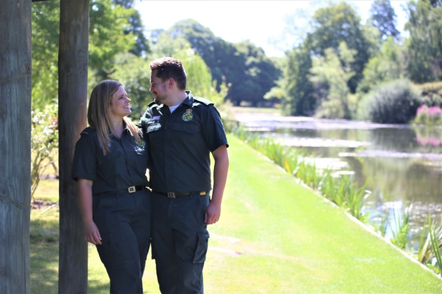 couple in paramedic clothes outside posing
