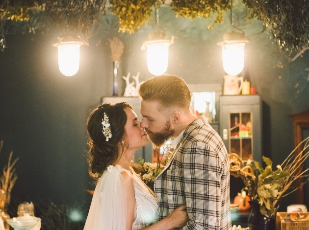 couple on wedding day in doors candle light groom in checked jacket