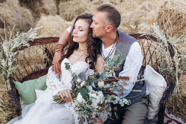 couple in relaxed wedding attire sitting on chair in front of haybales