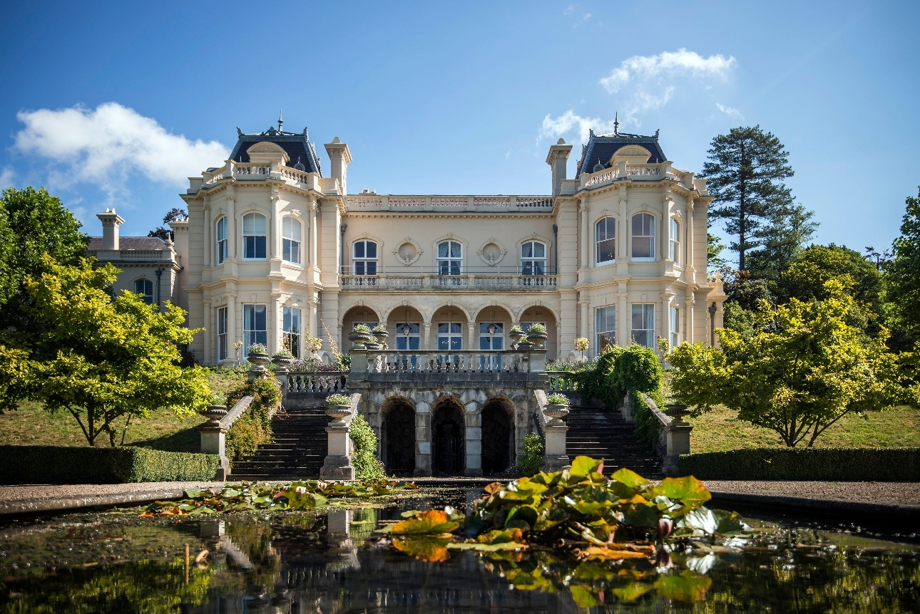 grand white victorian house with formal gardens