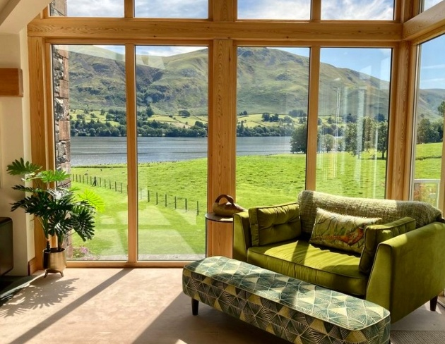 sofa in front of large window looking out to hills